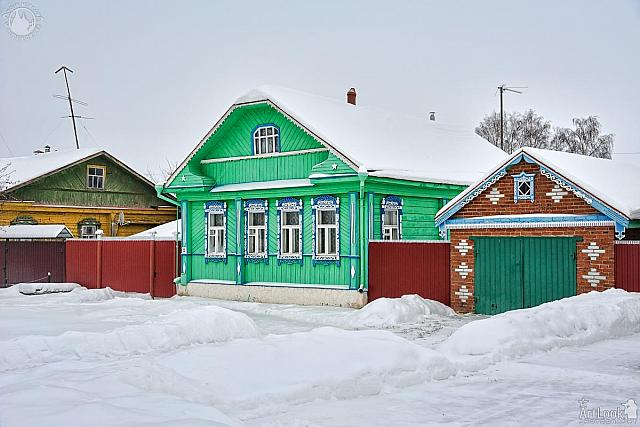 Green Wooden House with Garage on Pushkarskaya Street in Wintert