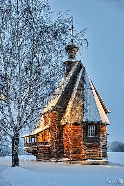 Old Wooden Church Framed by Tree in Winter Twilight