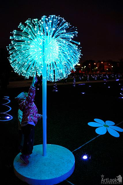 A Kid Touching a Neon Dandelion in Tsaritsyno Park