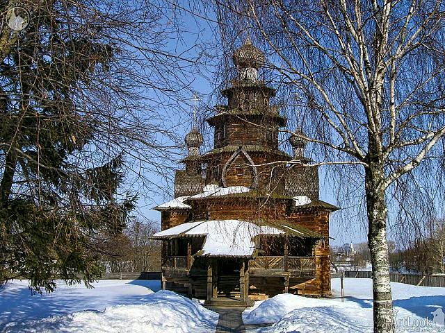 Wooden Transfiguration Church behind Trees in Snow