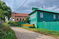 Green Wooden House on a Small Passage