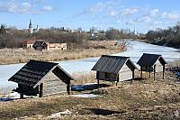 Three old barns on stilts near frozen Kamenka river