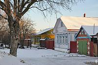 Wooden House on Pushkarskaya Street Framed by Tree in Winter