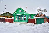 Green Wooden House with Garage on Pushkarskaya Street in Winter
