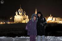 In Background of Illuminated Suzdal Kremlin in Winter Evening